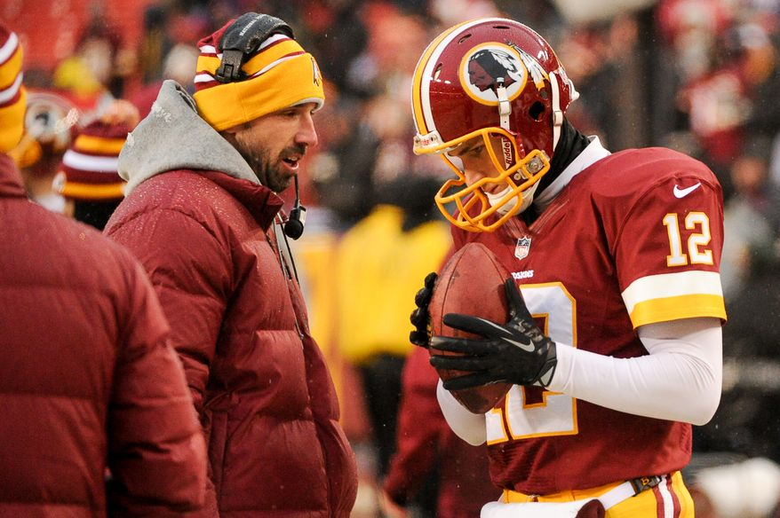 Washington Redskins offensive coach Kyle Shanahan, left, talks with Washington Redskins quarterback Kirk Cousins (12) as he warms up on the sideline to go into the game after Washington Redskins quarterback Robert Griffin III (10) is pulled from the game as the Washington Redskins lose to the Kansas City Chiefs 45-10 at FedExField, Landover, Md., Sunday, December 8, 2013. (Andrew Harnik/The Washington Times)