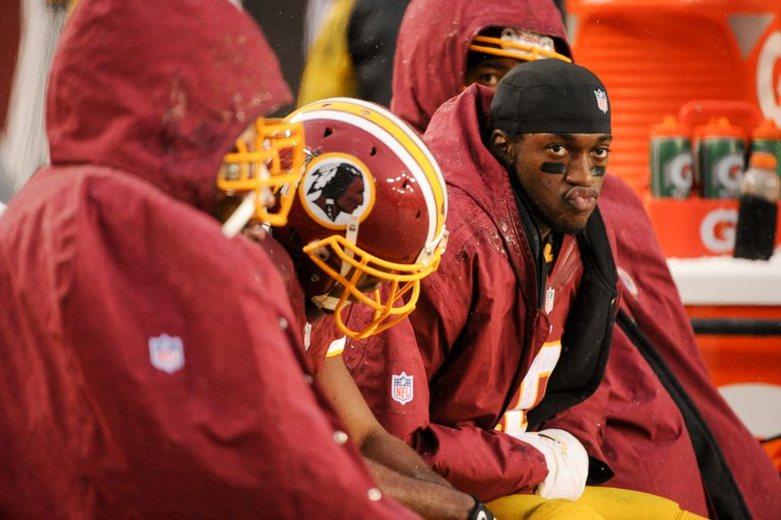 Washington Redskins quarterback Robert Griffin III (10), right, sits on the sideline in the fourth quarter after being pulled from the game as the Washington Redskins go on to lose to the Kansas City Chiefs 45-10 at FedExField, Landover, Md., Sunday, December 8, 2013. (Andrew Harnik/The Washington Times)