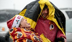 Sam Doss, 9, of Virginia Beach sticks his tongue out to collect snowflakes as he and family friend Mark Lewis of Alexandria get ready to head into FedEx Field as the Washington Redskins prepare to play the Kansas City Chiefs in snowy conditions in Landover, Md., on Sunday, Dec. 8, 2013. (Andrew Harnik/The Washington Times)