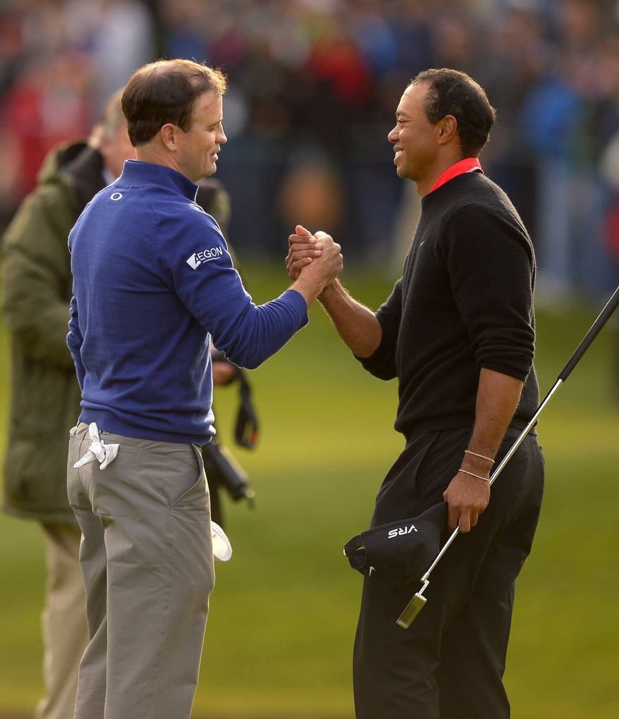 Tiger Woods, right, congratulates Zach Johnson after Johnson won the first playoff hole to win the Northwestern Mutual World Challenge golf tournament at Sherwood Country Club, Sunday, Dec. 8, 2013, in Thousand Oaks, Calif. (AP Photo/Mark J. Terrill)