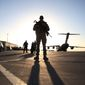 A solider stands guard near a military aircraft in Kandahar, Afghanistan, Sunday, Dec. 8, 2013. U.S. Secretary of Defense Chuck Hagel traveled to Kandahar Air Base to speak with U.S. troops and thank them for being deployed for the holidays. (AP Photo/Mark Wilson, Pool)