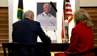 "Vice President Joe Biden, left, accompanied by his wife wife Jill Biden, signs a condolence book inside the South African Embassy in Washington, Monday, Dec. 9, 2013, as they paid their respects to former South African President Nelson Mandela. During the visit Biden said that the former president was, ""the most remarkable man I met in my whole career."" President Obama is en route to South Africa to attend a Tuesday memorial service for Mandela. (AP Photo/Jacquelyn Martin)"