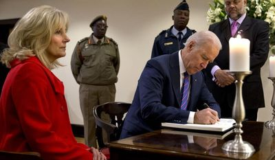 Vice President Joe Biden, accompanied by his wife Jill, signs a condolence book inside the South African Embassy in Washington, Monday, Dec. 9, 2013, as they paid their respects to former South African President Nelson Mandela. (AP Photo/Jacquelyn Martin)