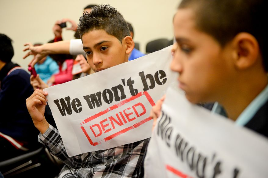 """Brothers Charlie, 11, left, and Anthony Hoz, 13, right, of Homestead, Fla., who's father was deported to Mexico this year and whose mother is also undocumented, hold up banners that read, """"We won't be Denied,"""" As they and other children of deportees call on congress to pass immigration reform at a press conference organized by members of We Belong Together on Capitol Hill, Washington, D.C., Monday, December 9, 2013. (Andrew Harnik/The Washington Times)"""
