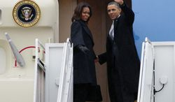 President Barack Obama, accompanied by first lady Michelle Obama, waves prior to boarding Air Force One at Andrews Air Force Base, Md., Monday, Dec. 9, 2013, before traveling to South Africa for a memorial service in honor of Nelson Mandela. ( AP Photo/Jose Luis Magana)