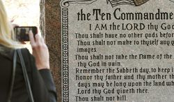 "** FILE ** On Nov. 15, 2012, a woman photographs a granite monument engraved with the Ten Commandments after it was erected on the north side of the Capitol in Oklahoma City. The word ""Sabbath"" was misspelled on the monument. (AP Photo/The Oklahoman, Jim Beckel)"