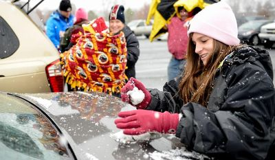 Savannah Doss, 11, of Virginia Beach makes a snowball in the parking lot of FedEx Field as she and her family get ready to head into the stadium for an NFL game between the Washington Redskins and the Kansas City Chiefs in Landover, Md., on Sunday, Dec. 8, 2013. (Andrew Harnik/The Washington Times)