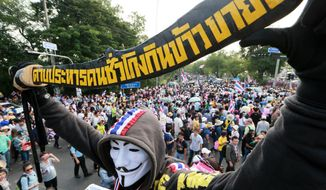 "A masked Thai anti-government protester holds a banner that reads ""execute bad people"" while gathering outside the Government House following a march rally Monday, Dec. 9, 2013 in Bangkok, Thailand. Desperate to defuse Thailand's deepening political crisis, Prime Minister Yingluck Shinawatra on Monday said she is dissolving the lower house of Parliament and called for early elections. But the moves did nothing to stem a growing tide of more than 150,000 protesters vowing to overthrow her in one of the nation's largest demonstrations in years. (AP Photo/Wason Wanichakorn)"