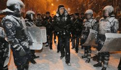 Ukrainian lawmaker and chairman of the opposition party Udar (Punch), WBC heavyweight boxing champion Vitali Klitschko surrounded by police trying to stop possible clashes between police and Pro-European Union activists in Kiev, Ukraine, Monday, Dec. 9, 2013. Hundreds of police in full riot gear on Monday flooded the center of Kiev key sites of mass anti-government protests that have gripped the capital for weeks, raising fears of a crackdown.(AP Photo/Efrem Lukatsky)