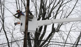 Baltimore Gas & Electric lineman Jim Thompson repairs a power line that was damaged by a tree limb in Towson, Md., Monday, Dec. 9, 2013, after a winter storm dumped a mix of snow, freezing rain and sleet on the Mid-Atlantic region. (AP Photo/Steve Ruark)
