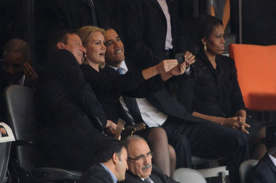 U.S. President  Barack Obama (R) and British Prime Minister David Cameron pose for a picture with Denmark's Prime Minister Helle Thorning Schmidt (C) next to US First Lady Michelle Obama (R) during the memorial service of South African former president Nelson Mandela at the FNB Stadium (Soccer City) in Johannesburg on December 10, 2013. Mandela, the revered icon of the anti-apartheid struggle in South Africa and one of the towering political figures of the 20th century, died in Johannesburg on December 5 at age 95.  (ROBERTO SCHMIDT/AFP/Getty Images)