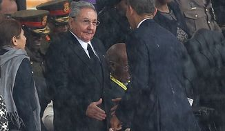 US President Barack Obama shakes hands with Cuban President Raul Castro at the FNB Stadium in Soweto, South Africa, in the rain for a memorial service for former South African President Nelson Mandela, Tuesday Dec. 10, 2013. The handshake between the leaders of the two Cold War enemies came during a ceremony that's focused on Mandela's legacy of reconciliation. Hundreds of foreign dignitaries and world heads of states gather Tuesday with thousands of South African people to celebrate the life, and mark the death, of Nelson Mandela who has became a global symbol of reconciliation. (AP Photo) SOUTH AFRICA OUT