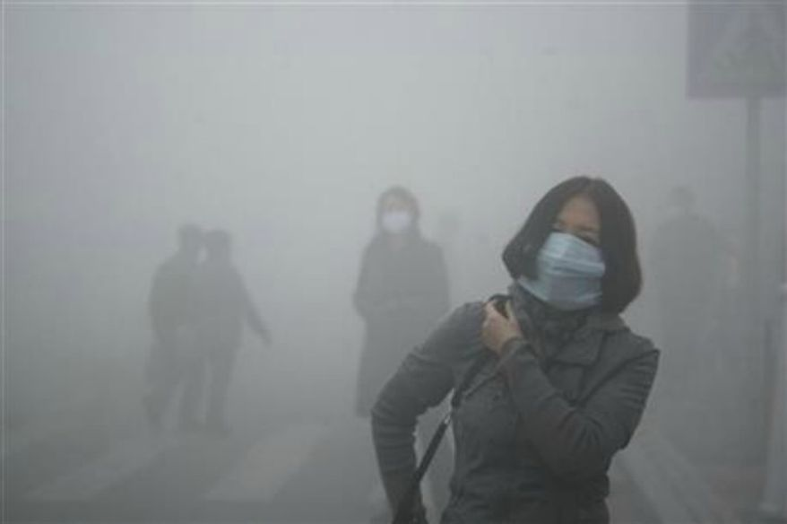 ** FILE ** A woman wearing a mask walks through a street covered by dense smog in Harbin, China, on Monday, Oct. 21, 2013. (Associated Press)