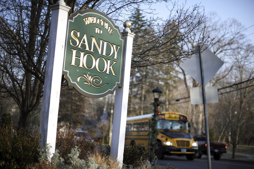FILE - In this Dec. 4, 2013 file photo, a school bus drives past a lamppost decorated for the holidays, and a sign reading Welcome to Sandy Hook, in Newtown, Conn. With winter on their doorstep once again, the people of Newtown are bracing for the day everyone there simply calls 12/14 - referring to the day in 2012 with 26 people were killed by a gunman inside Sandy Hook Elementary School. (AP Photo/Jessica Hill, File)