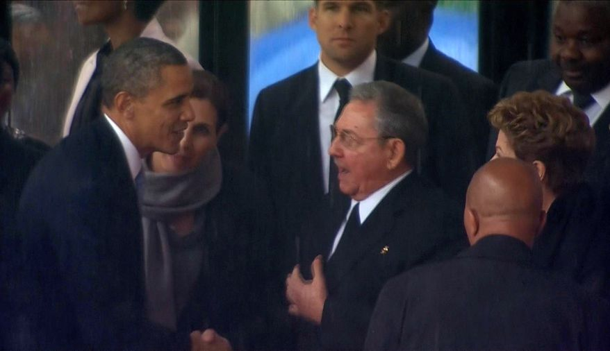 In this image from TV, U.S. President Barack Obama shakes hands with Cuban President Raul Castro at the FNB Stadium in Soweto, South Africa, in the rain for a memorial service for former South African President Nelson Mandela, Tuesday Dec. 10, 2013. (AP Photo/SABC Pool)