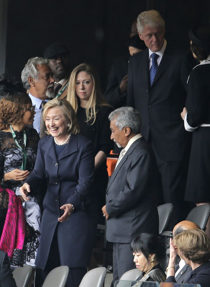 Former U.S. Secretary of State Hillary Rodham Clinton, former U.S. President Bill Clinton and their daughter Chelsea arrive for the memorial service for former South African president Nelson Mandela at the FNB Stadium in Soweto, near Johannesburg, South Africa, Tuesday Dec. 10, 2013. (AP Photo/Peter Dejong)