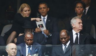 President Barack Obama talks with Danish prime minister, Helle Thorning-Schmidt, left, as first lady Michelle Obama looks on at right during the memorial service for former South African president Nelson Mandela at the FNB Stadium in Soweto, near Johannesburg, South Africa, Tuesday Dec. 10, 2013. (AP Photo/Matt Dunham)
