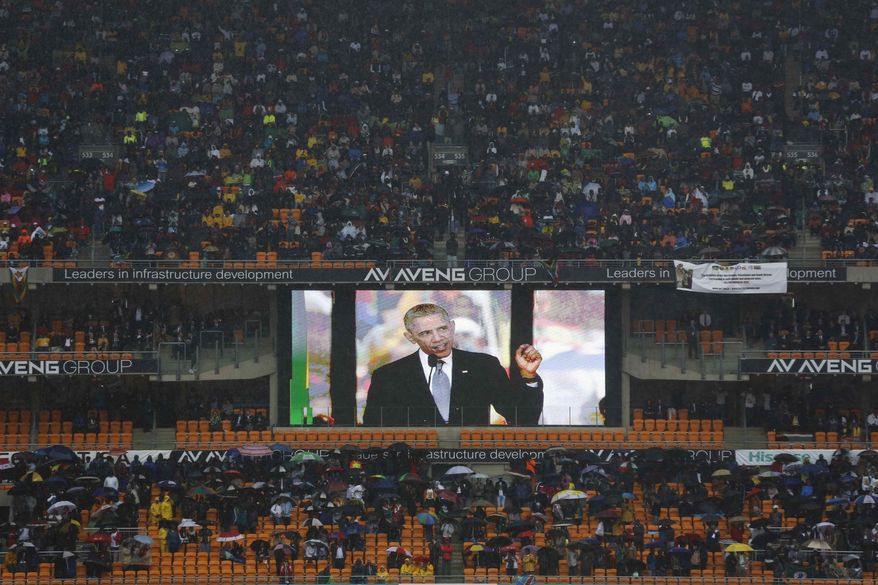 An image of President Barrack Obama is flashed on a screen as he makes his speech during the memorial service for former South African president Nelson Mandela at the FNB Stadium in Soweto, near Johannesburg, South Africa, Tuesday Dec. 10, 2013.  (AP Photo/Markus Schreiber)