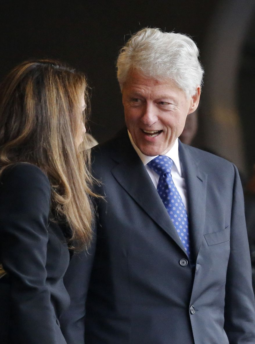 Former President Bill Clinton speaks with Jordan's Queen Rania during the memorial service for former South African President Nelson Mandela at the FNB stadium in Johannesburg, South Africa Tuesday, Dec. 10, 2013. (AP Photo/Ben Curtis)