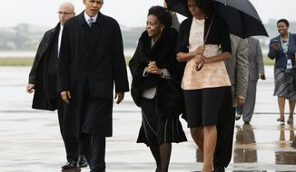 President Barack Obama, left, and first lady Michelle Obama, right, arrive at Waterkloof Air Base for a memorial service in honor of former South African leader Nelson Mandela on Tuesday, Dec. 10, 2013, in Centurion, South Africa. World leaders, celebrities, and citizens from all walks of life gathered for a memorial service on Tuesday to pay respects to Mandela. (AP Photo/ Evan Vucci)