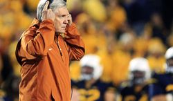 FILE - In this Nov. 9, 2013, file photo, Texas coach Mack Brown walks across the field after an injury to one of his players in the second quarter of an NCAA college football game against West Virginia in Morgantown, W.Va. Brown's attorney says the Texas coach has not resigned, denying a report on Tuesday, Dec. 10, 2013, that Brown was ready to step down after 16 seasons with the Longhorns. (AP Photo/Christopher Jackson, File)