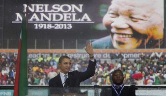 In this Dec. 10, 2013, photo, President Barack Obama waves as he arrives to speak at the memorial service for former South African president Nelson Mandela at the FNB Stadium in the Johannesburg, South Africa township of Soweto. (AP Photo/Evan Vucci)