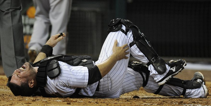 Houston Astros catcher Humberto Quintero grabs his leg after a collision at home plate with Arizona Diamondbacks' Ryan Roberts during the seventh inning of a baseball game on Friday, May 27, 2011, in Houston. Quintero left the game with a sprained ankle. (AP Photo/Pat Sullivan)