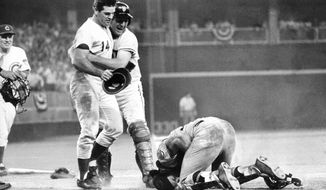 National League's Pete Rose, left, is hugged by his teammate Dick Dietz while American League's catcher Ray Fosse lies injured on the ground, after Rose crashed into him to score the game-winning run for the National League team, in the 1970 All-Star Game, in Cincinnati, Ohio, July 14, 1970. Fosse suffered a fractured shoulder in the collision. (AP Photo)