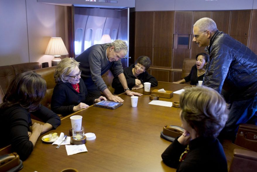 ** FILE ** Aboard Air Force One, former President Bush shows photos of his paintings to, from left, first lady Michelle Obama, former Secretary of State Hillary Clinton, Valerie Jarrett, National Security Adviser Susan E. Rice, Attorney General Eric Holder and former first lady Laura Bush, Dec. 9, 2013. (Official White House Photo by Pete Souza)