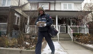 A Canada Post employee delivers mail and parcels to residential homes in Toronto on Wednesday, Dec. 11, 2013. The nation's postal service said it will phase out home delivery within urban centers within the next five years as it begins to post significant financial losses because of growing use of digital communication. Canada Post, a government corporation, said it will replace foot delivery with community mail boxes, (AP Photo/The Canadian Press, Nathan Denette)