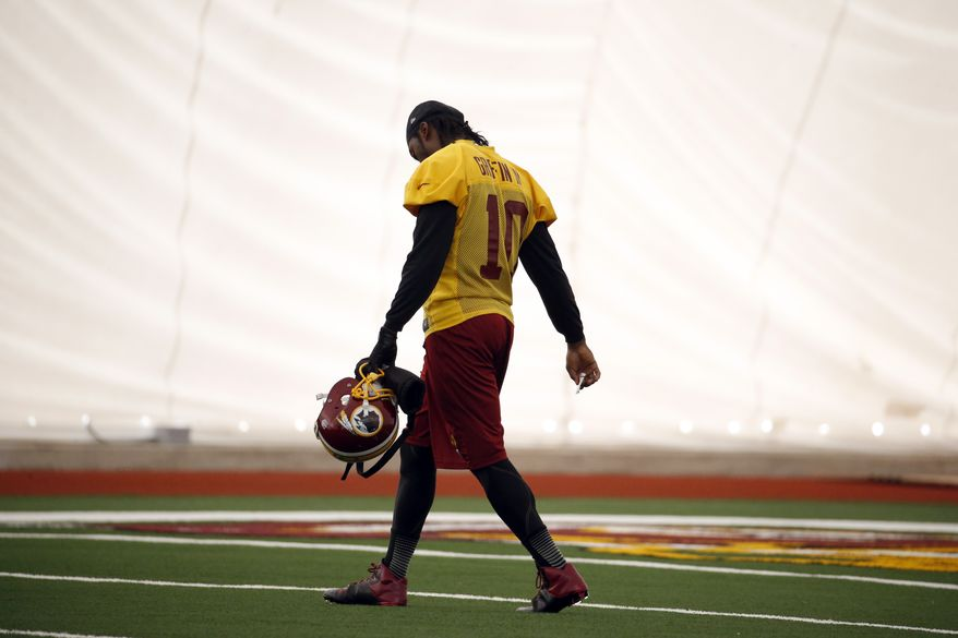 Washington Redskins quarterback Robert Griffin III, walks on the field during an NFL football practice Wednesday, Dec. 11, 2013, in Ashburn, Va. Quarterback Kirk Cousins will start for the Redskins on Sunday, and Griffin III will be the No. 3 quarterback behind Rex Grossman. (AP Photo/Alex Brandon)