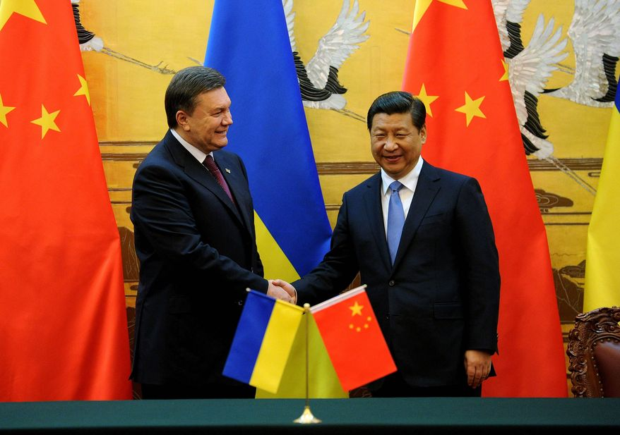 Ukrainian President Viktor Yanukovych shakes hands with Chinese President Xi Jinping during a signing ceremony at the Great Hall of the People in Beijing last week. Mr. Yanukovych's visit is aimed at gaining Chinese support for Ukraine's battered economy. The country's economic malaise has helped fuel ongoing protests in Kiev. (ASSOCIATED PRESS)