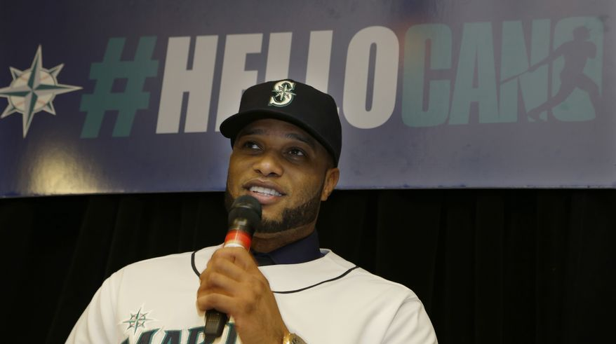 """Robinson Cano sits under a sign that reads """"#HelloCano"""" as he talks to fans gathered at an event to honor him as the newest member of the Seattle Mariners baseball team on Thursday, Dec. 12, 2013, in Seattle. (AP Photo/Ted S. Warren)"""