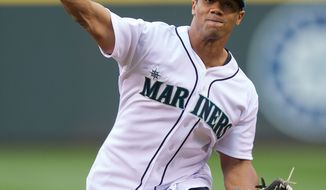 FILE - In this June 7, 2013 file photo, Seattle Seahawks quarterback Russell Wilson throws out the ceremonial first pitch before a baseball game between the Seattle Mariners and the New York Yankees, in Seattle. Wilson has been selected by the Texas Rangers from the Colorado Rockies in the Triple-A portion of baseball's winter meeting draft. The Rangers made the Rule 5 pick Thursday, Dec. 12, 2013. Wilson, who played minor league baseball for parts of two seasons before becoming an NFL star, will be placed on Texas' restricted list. (AP Photo/Stephen Brashear, File)