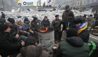 Pro-European Union activists warm themselves in front of barricades at their tent camp in Independence Square in Kiev on Wednesday, Dec. 11, 2013. Ukraine was thrown into crisis last month when President Viktor Yanukovych suddenly backed away from a long-awaited political and economic agreement with the European Union, deciding to focus instead on restoring trade ties with Russia.  (AP Photo/Sergei Chuzavkov)