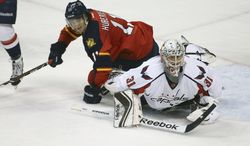 After blocking a shot-on-goal Washington Capitals goalie Philipp Grubauer (31) and Florida Panthers Jonathan Huberdeau (11) look for the puck during the second period of a NHL hockey game in Sunrise, Fla., Friday, Dec. 13, 2013.  (AP Photo/J Pat Carter)