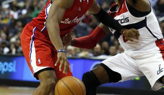 Los Angeles Clippers guard Chris Paul (3) drives against Washington Wizards guard John Wall (2) in the first half of an NBA basketball game, Saturday, Dec. 14, 2013, in Washington. (AP Photo/Alex Brandon)