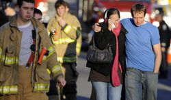 In this Dec. 14, 2012, file photo, Robert and Alissa Parker, at right, leave a firehouse staging area following a shooting at the Sandy Hook Elementary School in Newtown, Conn. Gunman Adam Lanza opened fire inside the school, killing 26 children and adults, including the Parkers' daughter Emilie Parker, 6. (AP Photo/Jessica Hill, File)