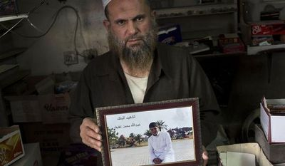 """In this Friday, Oct. 25, 2013 photo, Mohammed Siddeh, 52, at his workshop in Russeifa, outside Amman, Jordan, holds a picture of his son, Abdullah Siddeh, with the boy's name inscribed on the print in Arabic. On his last day as an ordinary teenager, Abdullah kept to his daily routine: He filled in for his father at the small family grocery in the afternoon, asked his mother at home about dinner and then played soccer with friends at the nearby high school. After the game, the 17-year-old slipped out of his hometown in central Jordan. Six months later, Mohammed got a phone call from Syria. His son had blown himself up in a rebel attack on a police station in Syrian capital of Damascus, the unknown man on the line told him. Mohammed said he asked the man how he could bring his son's remains home for burial. The reply: """"There is no body."""" (AP Photo/Manu Brabo)"""