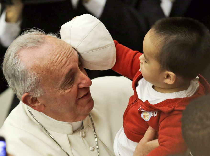 A child takes off Pope Francis' white zucchetto, or skullcap, during a meeting with children and volunteers of the Santa Marta Vatican Institute, at the Vatican, Saturday, Dec. 14, 2013. (AP Photo/Gregorio Borgia)