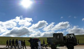 The casket of former South African President Nelson Mandela is carried on a gun carriage in a military parade from the family home to the funeral tent before his burial in Qunu, South Africa, on Sunday, Dec. 15, 2013. (AP Photo/Elmond Jiyane, GCIS)