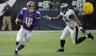 Minnesota Vikings quarterback Matt Cassel, left, runs from Philadelphia Eagles defensive end Vinny Curry during the first half of an NFL football game against the Philadelphia Eagles, Sunday, Dec. 15, 2013, in Minneapolis. (AP Photo/Ann Heisenfelt)