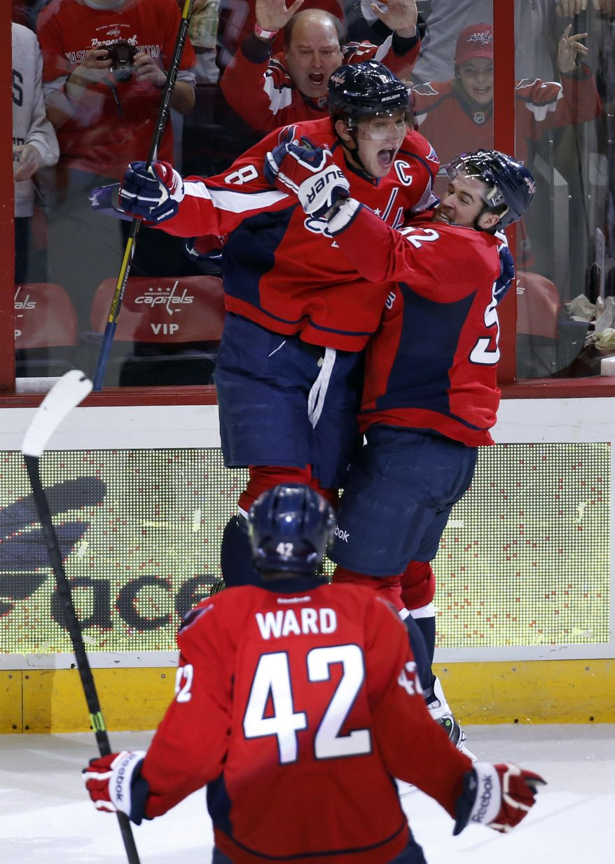 Washington Capitals right wing Alex Ovechkin (8), from Russia, celebrates his goal with defenseman Mike Green (52) as right wing Joel Ward (42) comes comes join them, in the third period of an NHL hockey game, Sunday, Dec. 15, 2013, in Washington. Ovechkin's goal sent the game into overtime and the Capitals won 5-4 in a shootout. (AP Photo/Alex Brandon)