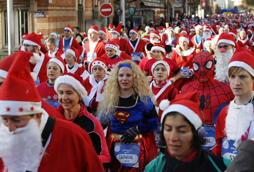 """Runners, dressed as Santa Claus, and one dressed as Superwoman, take part in the 37th """"Christmas Corrida Race"""" in the streets of Issy Les Moulineaux, on the western outskirts of Paris, Sunday, Dec. 15, 2013. (AP Photo/Francois Mori)"""