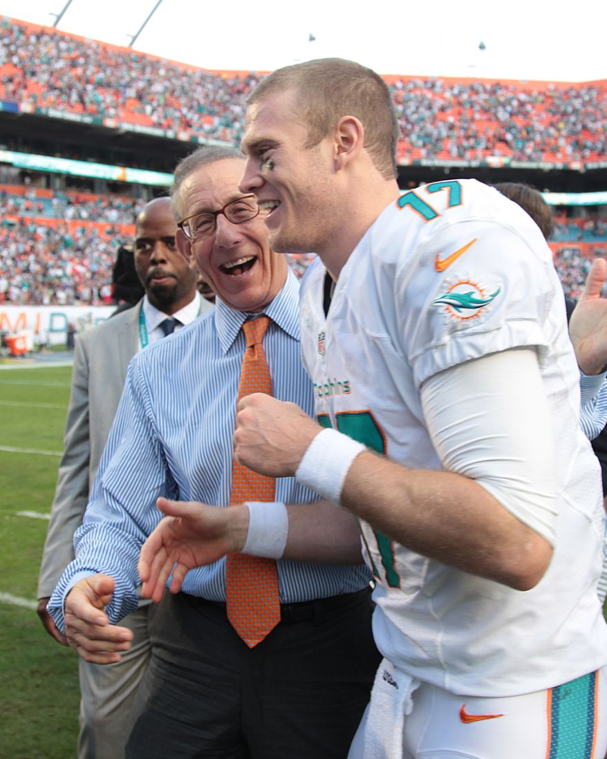 Miami Dolphins owner Joe Philbin, front left, congratulates quarterback Ryan Tannehill at the end of an NFL football game against the New England Patriots, Sunday, Dec. 15, 2013, in Miami Gardens, Fla. The Dolphins defeated the Patriots 24-20. (AP Photo/J Pat Carter)