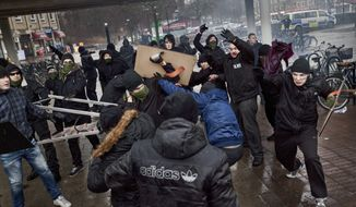 Right-wing extremists, background, clash with anti-nazi demonstrators in the Stockholm suburb of Karrtorp, Sweden, Sunday, Dec. 15, 2013. There were several injuries and dozens were arrested.    (AP photo / TT News Agency / Hampus Andersson)  SWEDEN OUT