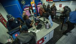 People line up Monday at the DC Lottery store at Union Station to purchase Mega Million lottery tickets for a chance to win the $586 million jackpot. (andrew s. geraci/the Washington Times)