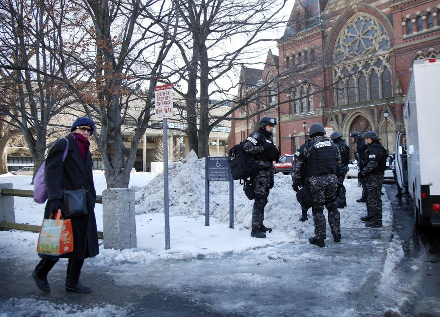 ** FILE ** A pedestrian walks by as SWAT team members assemble outside a building at Harvard University in Cambridge, Mass., Monday, Dec. 16, 2013. Four buildings on campus were evacuated after campus police received an unconfirmed report that explosives may have been placed inside, interrupting final exams. (AP Photo/Elise Amendola)