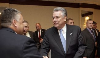 U.S. Rep. Peter King, R-N.Y., right, shakes hands with members of the Northeast Regional Troopers Coalition, Monday, Dec. 16, 2013 in Concord, N.H. King is considered a possible presidential candidate for 2016. (AP Photo/Jim Cole)