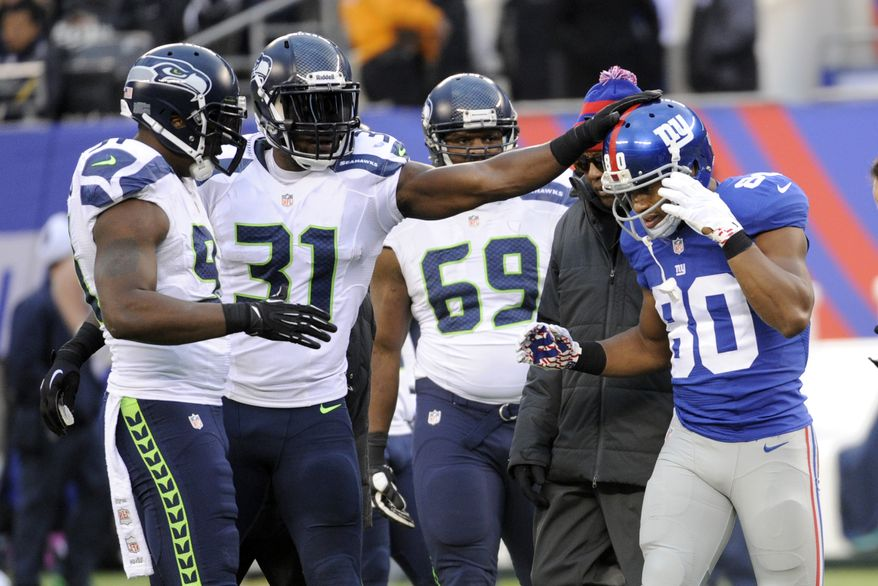 Seattle Seahawks' Kam Chacellor (31) pats New York Giants' Victor Cruz (80) as Cruz leaves the field with an injury during the second half of an NFL football game, Sunday, Dec. 15, 2013, in East Rutherford, N.J. (AP Photo/Bill Kostroun)